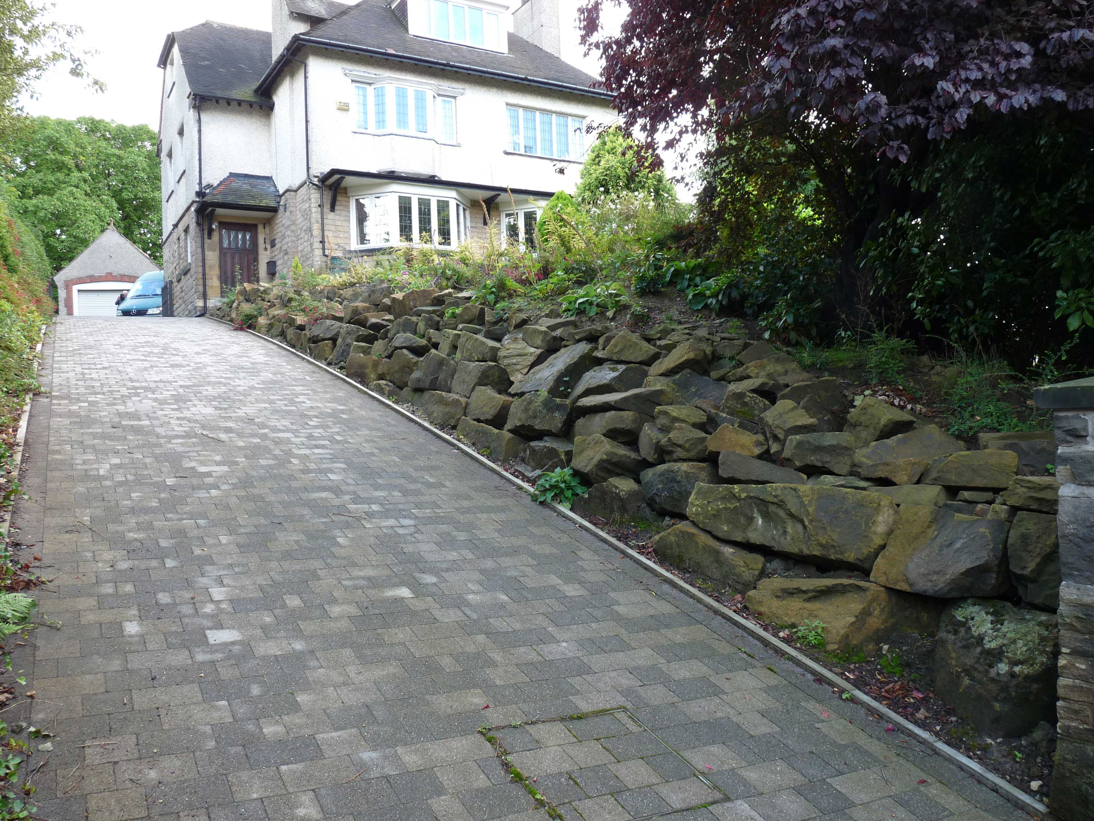 Landscaping to the side. Rocky wall face. Agrent Paving